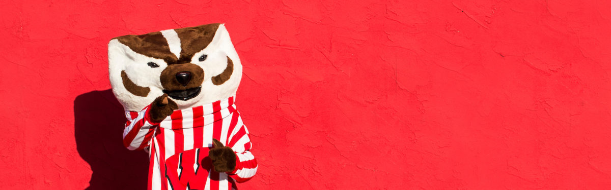Image of Bucky Badger standing by a red wall pointing his index finger toward the viewer.